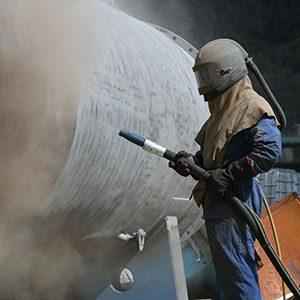 A worker sandblasts metal