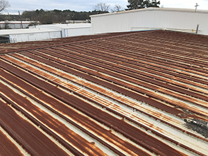 Before picture of a rusty commercial roof in need or repair