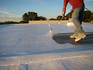 A Capital Coating employee applies a protective coating on a commercial roof