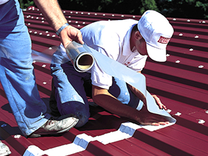 Two workers apply material to seal cracks on a commercial roof
