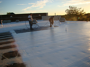 two workers apply epdm roof coating material to a flat roof