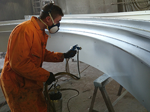 A worker applies a spray coating on metal