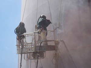 Two employees apply a paint coating on the outside of a commercial facility