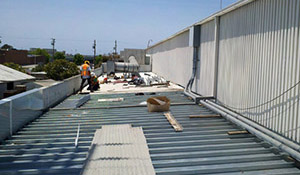 Employees restore a metal rooftop with a roof coating