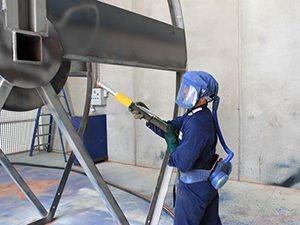 An employee sandblasts a piece of metal equipment