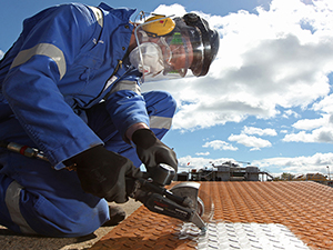 A worker applies a coating to a metal commercial roof