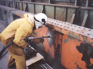 An employee prepares the surface of metal for painting