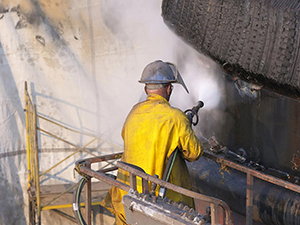 An employee sprays a coating of paint on the walls of a facility