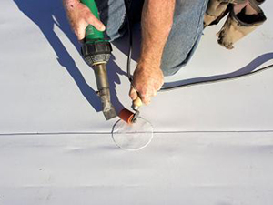 repairing a commercial roof with rubber roofing material