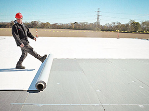 rubber material being unrolled on a commercial flat top roof