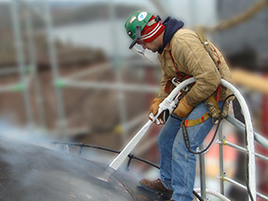 A worker applies a coating on a domed metal roof