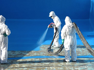 Three employees apply blue paint to a surface