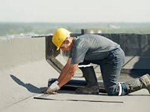 A worker performs roof maintenance on a commercial rooftop