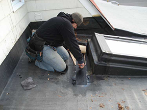 An employee repairs a leak on a commercial roof with material