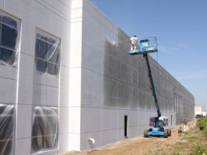 A Capital Coating employee applies a paint coating on the outside concrete wall of a commercial facility